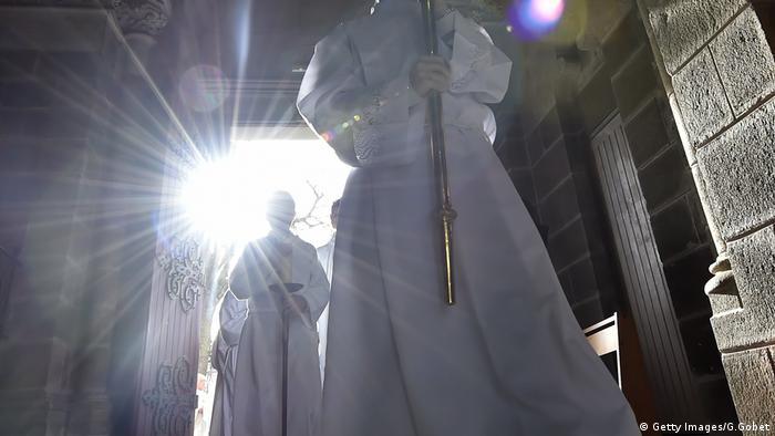 Padres entram em igreja. Sol brilha ao fundo