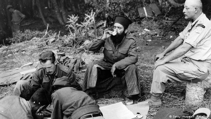Officers plan the assault on Mount Kiapha at Mount Lyoku during the Greek Civil War, while a Greek Orthodox priest drinks coffee (Photo by Federico Patellani/Getty Images)