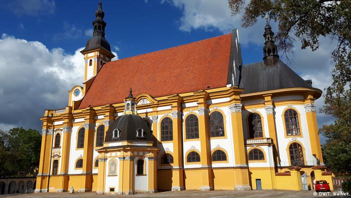 Yellow Baroque church with a red roof in Neuzelle (DW/T. Walker)