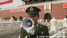A Chinese paramilitary policeman uses a megaphone to control visitors to Tiananmen gate as the Chinese Communist Party's 17th five-yearly Congress continues in Beijing 18 October 2007. Security remains tight in the capital after President Hu Jintao opened China's biggest political event in five years with pledges to curb the worst excesses of breakneck economic growth and implement limited political reforms. AFP PHOTO/Peter PARKS (Photo credit should read PETER PARKS/AFP/Getty Images)