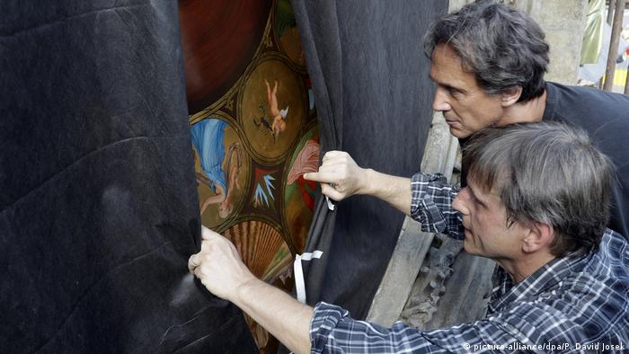 A painter examines a restored copy of the calendar illustrations (picture-alliance/dpa/P. David Josek)