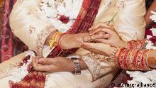 Indische Braut steckt Ehering auf den Finger ihres Bräutigams