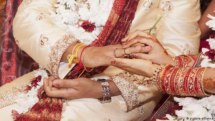 Indische Braut steckt Ehering auf den Finger ihres Bräutigams (picture-alliance)
