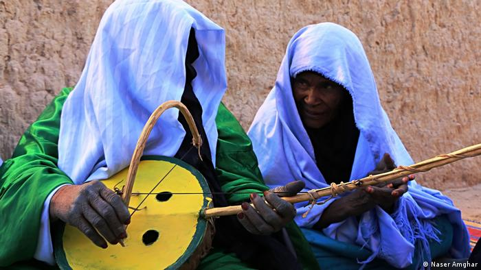 The photos reflect Libyan landscapes, customs, traditions and crafts. One of the women in this photo by Naser Amghar plays a stringed gourd, a traditional musical instrument. (Naser Amghar)