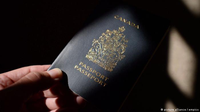 A hand holds a Canadian passport