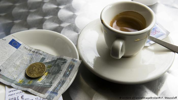 Cup of espresso with euro note and coin on plate