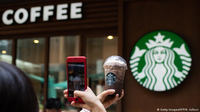 A woman takes a picture of her beverage at a Starbucks cafe