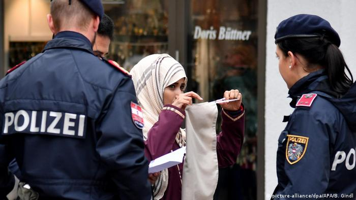 Two police officers speak with a woman in a headscarf