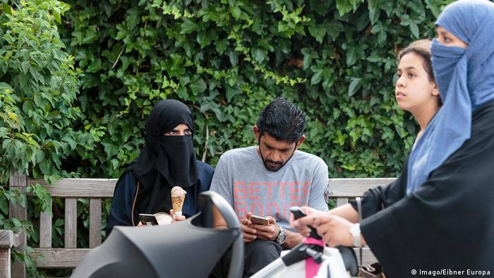 Österreich eine Frau in Burka gekleidet und ein Mann auf einer Parkbank in Zell am See (Imago/Eibner Europa)