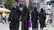Wohlhabende Frauen gehen in einer Wiener Einkaufsstrasse shoppen, gekleidet in Burkas | Verwendung weltweit