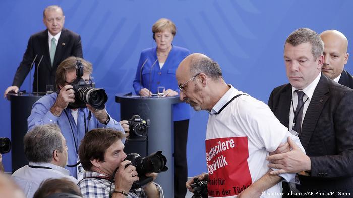 Deutschland | Protest T-Shirt auf PK vom Merkel und Erdogan (picture-alliance/AP Photo/M. Sohn)
