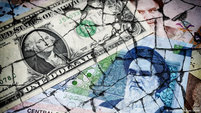 Iranian rial and US dollar on cracked ground