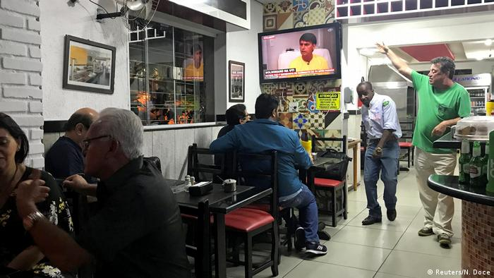 Pessoas em um bar assistem a entrevista com Bolsonaro na TV