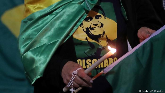 Apoiadora de Jair Bolsonaro veste camiseta de candidato e carrega vela acesa e terço