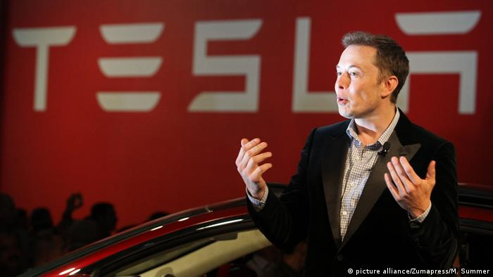 Musk gesturing in front of a Tesla logo and car (picture alliance/Zumapress/M. Summer)