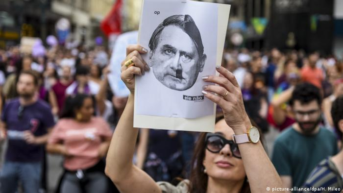 Woman holding up picture showing face of Bolsonaro combined with that of Hitler