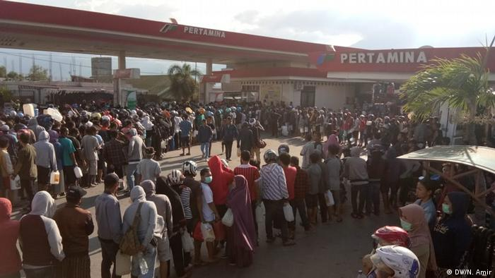A crowd of survivors stands in line before a gas station (DW/N. Amir)