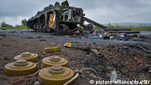 Ukraine Landminen vor einem zerstörten Panzer