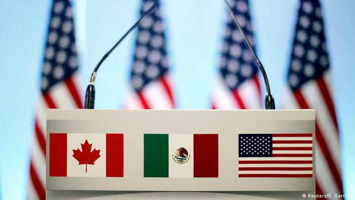 The Canadia, Mexican and US flags on a podium