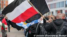 01.05.2018, Sachsen, Chemnitz: Ein Teilnehmer einer Demonstration von Rechtsextremisten geht mit einer Schwarz-weiß-roten Flagge. Anmelder ist die Neonazi-Partei Der III. Weg. Foto: Jan Woitas/dpa-Zentralbild/dpa   Verwendung weltweit