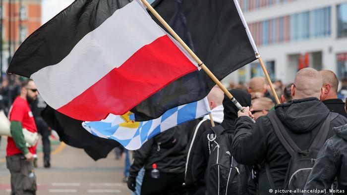 Homens de cabeça raspada empunham bandeiras em vermelho, branco e negro