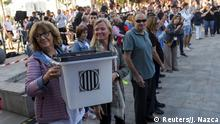 People pass a ballot box used during the banned referendum on independence during ceremonies marking the first anniversary of Catalonia's banned independence referendum in Sant Julia de Ramis, Spain, October 1, 2018. REUTERS/Jon Nazca