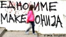 A person walking past graffiti on the Macedonia name change (DW/B. Georgievski)