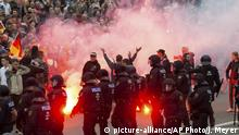 FILE - In this Aug. 27, 2018 photo protesters light fireworks during a far-right demonstration in Chemnitz, Germany. German prosecutors say they have ordered the arrest of six men on suspicion of forming a far-right terrorist organization in the eastern city of Chemnitz, where anti-migrant violence flared this summer. Prosecutors said in a statement the men planned to carry out armed attacks against foreigners and political enemies. (AP Photo/Jens Meyer, file)  