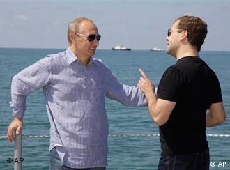 Дмитрий Медведев и Владимир путин разговоривают на фоне моря и кораблей