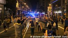 Pro-independence demonstrators stand on the middle of a street facing Catalan police officers during a protest In Barcelona, Spain, Monday, Oct. 1, 2018. Pro-secession activists in Spain's Catalonia region have turned out in large numbers to mark the first anniversary of their thwarted independence referendum with an evening march through downtown Barcelona that capped a day of noisy protests that blocked Catalan roads and train lines, among other largely non-violent demonstrations. (AP Photo/Felipe Dana)  