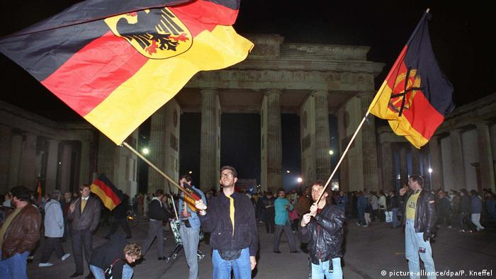 People hold flags from the former East and West Germany at the Brandenburg Gate on October 3, 1990 (picture-alliance/dpa/P. Kneffel)