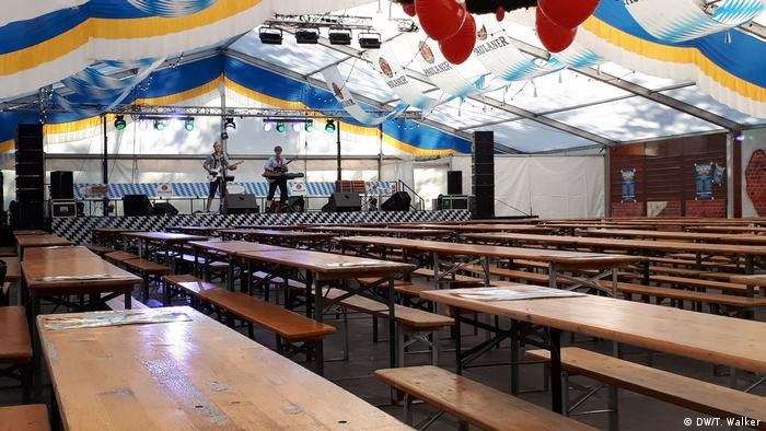 Lines of wooden tables in a big white tent at the Berlin Oktoberfest. Two members of a band play on a stage in the background