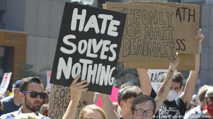 Protester holding up sign reading: 'Hate solves nothing'