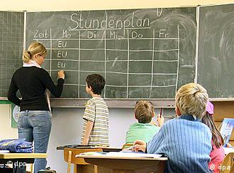 Students and a teacher work at a blackboard