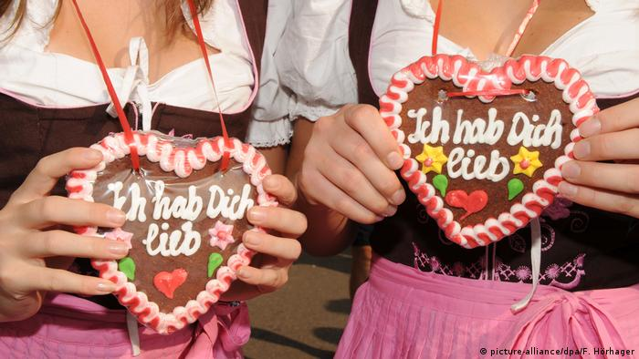 Women in dirndls holding cookie necklaces shaped as hearts (picture-alliance/dpa/F. Hörhager)