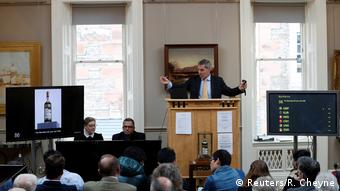 An auctioneer stands at a podium while bottle of whisky is showed on a screen (Reuters/R. Cheyne)