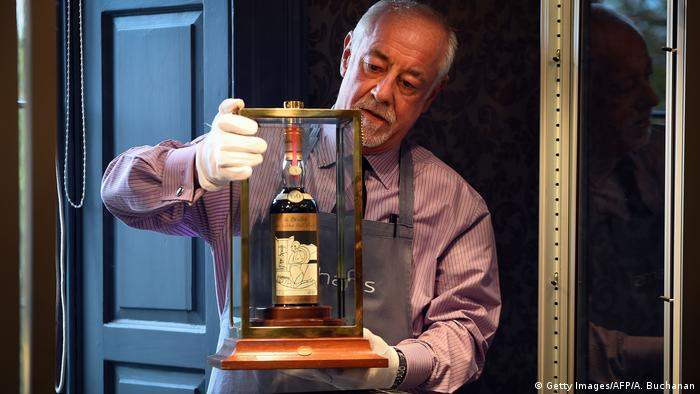 A man holds up a bottle of whisky in a glass case while wearing white gloves (Getty Images/AFP/A. Buchanan)