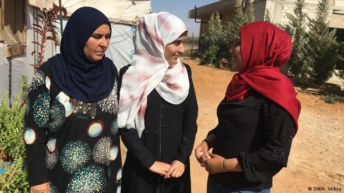 Three women in a refugee camp talking