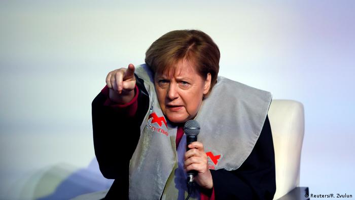 Merkel points her finger to take a question during a question and answer session at Haifa University (Reuters/R. Zvulun)