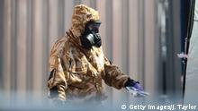 Emergency workers wear protective suits while searching around a house in the British town of Salisbury (Getty Images/J. Taylor)
