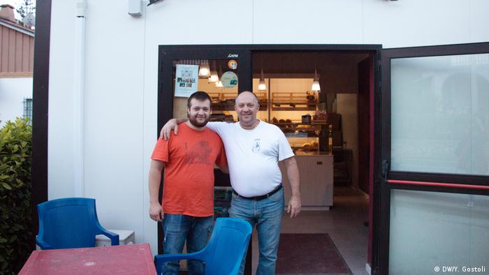 Two men standing outside their bakery in Visso