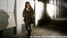 Symbolbild: Angst - Frau geht alleine nachts auf einer Straße und fühlt sich bedroht