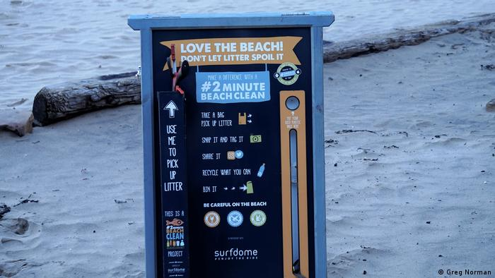 A sign on the beach that calls on people to collect trash