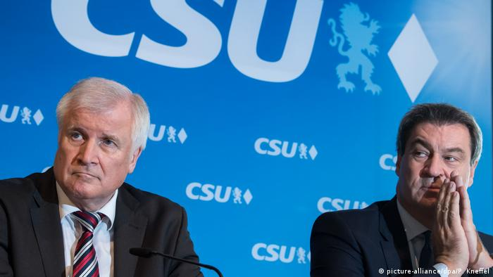 Seehofer and Söder look very unhappy in front of a CSU sign