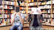 Ein Mann hält sich ein elektronisches Buch, E-Book-Reader, ein anderer Mann ein konventionelles Buch vor das Gesicht, in einer Buchhandlung, Regensburg, Bayern, Deutschland, Europa | Verwendung weltweit, Keine Weitergabe an Wiederverkäufer.