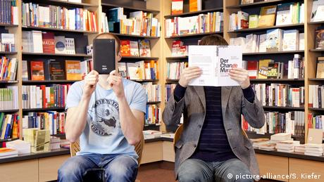 Stock photo of a man holding a book beside another man holding a tablet (picture-alliance/S. Kiefer)