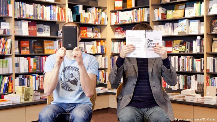 Symbolbild: Ein Mann hält sich ein elektronisches Buch, E-Book-Reader, ein anderer Mann ein konventionelles Buch vor das Gesicht