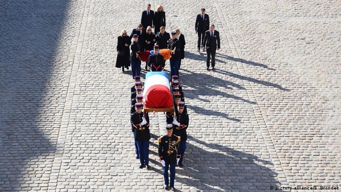 Caixão de Aznavour coberto pela bandeira da França é carregado por soldados no Palácio dos Inválidos