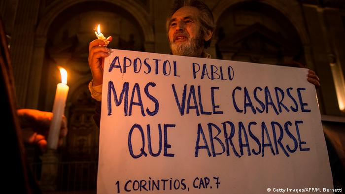 Man with candle holding banner saying 'It is better to marry than to burn with passion'