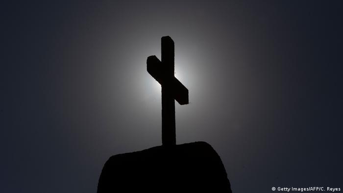 Cross standing in the dark before a hidden light source